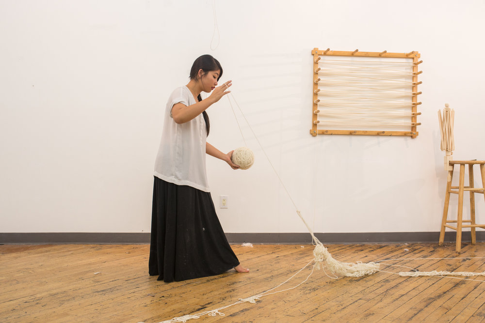 The artist pulls onto the knotted yarn with her right hand while holding on to the ball of untangle yarn with her left.