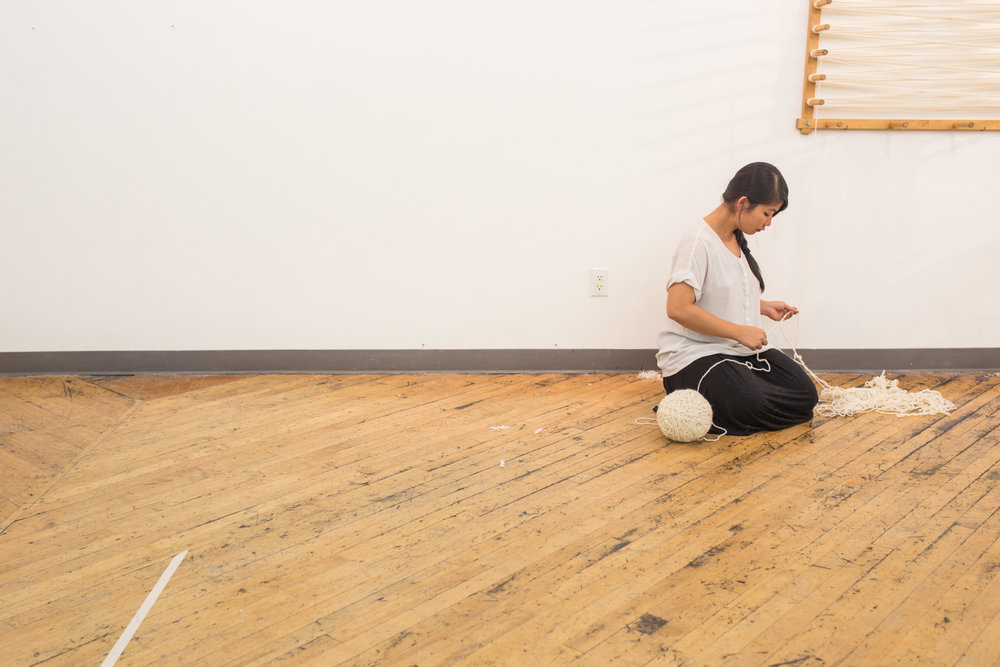 The artist kneels on the floor to untangle a knot. The ball of untangled yarn is almost at 8 inches in diameter.