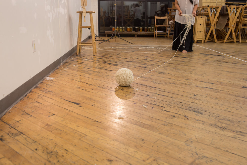 A large ball of untangled yarn is in the foreground. It's now around 9 inches in diameter. the artist is in the background untangling a small strand of knotted yarn.