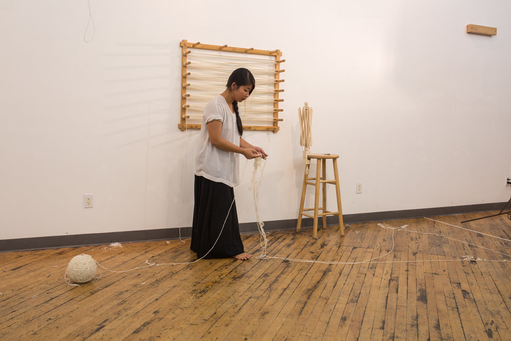 The artist holds the rest of the knotted yarn in her hand.