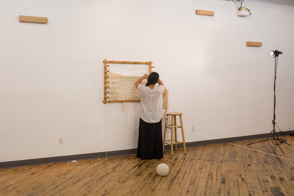 The ball of untangled yarn is now at around 10 inches in diameter. It's places on the floor. The artist turns around to cut off left over yarn from the warping board.