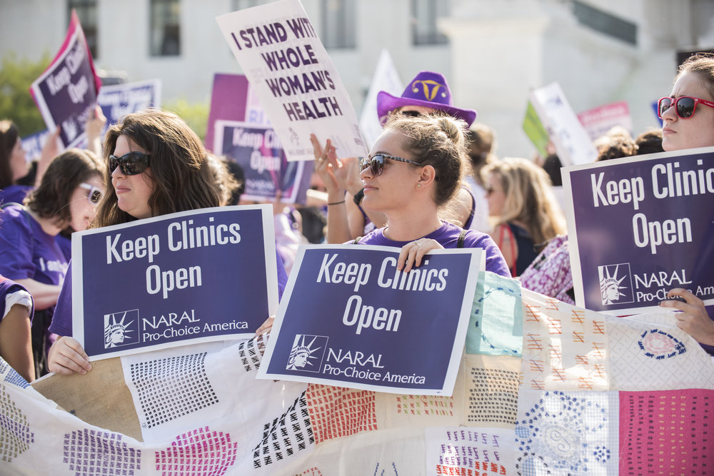 "Three women holding ""Keep Clinics Open"" signs while holding onto the quilt. Many supporters with protest signs are in the background."