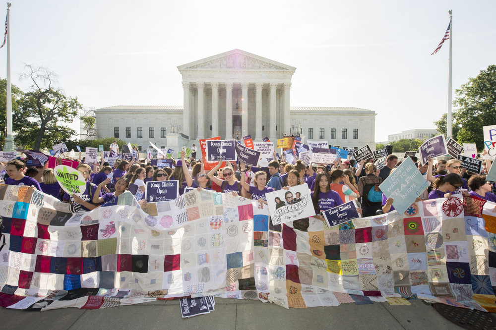 The middle of the quilt being held up by thirteen people with signs that support reproductive rights. The quilt is almost as tall as the supporters. The Supreme Court is centered and prominently in the background with a sea of people waiting for the Supreme Court decision in June. The sun is shinning down.