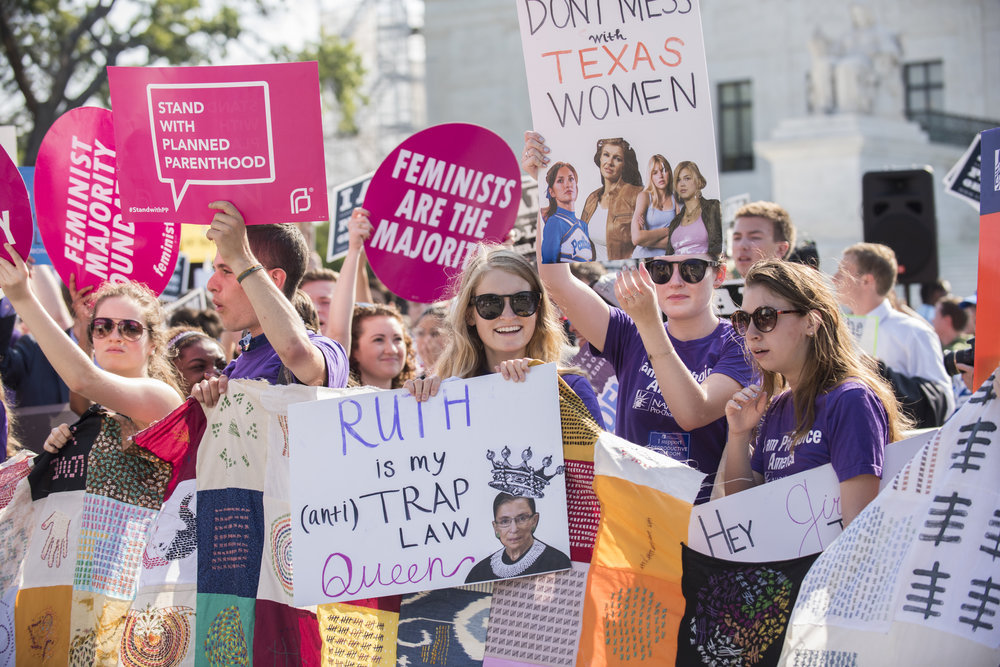 "Supporters holding the quilt with notable, homemade signs like ""Ruth Bader Ginsberg is my (anti) TRAP Law Queen"" and ""Don't Mess with Texas Women"" in June. Other supporters holding Planned Parenthood and Feminist Majority Foundation signs in the background."