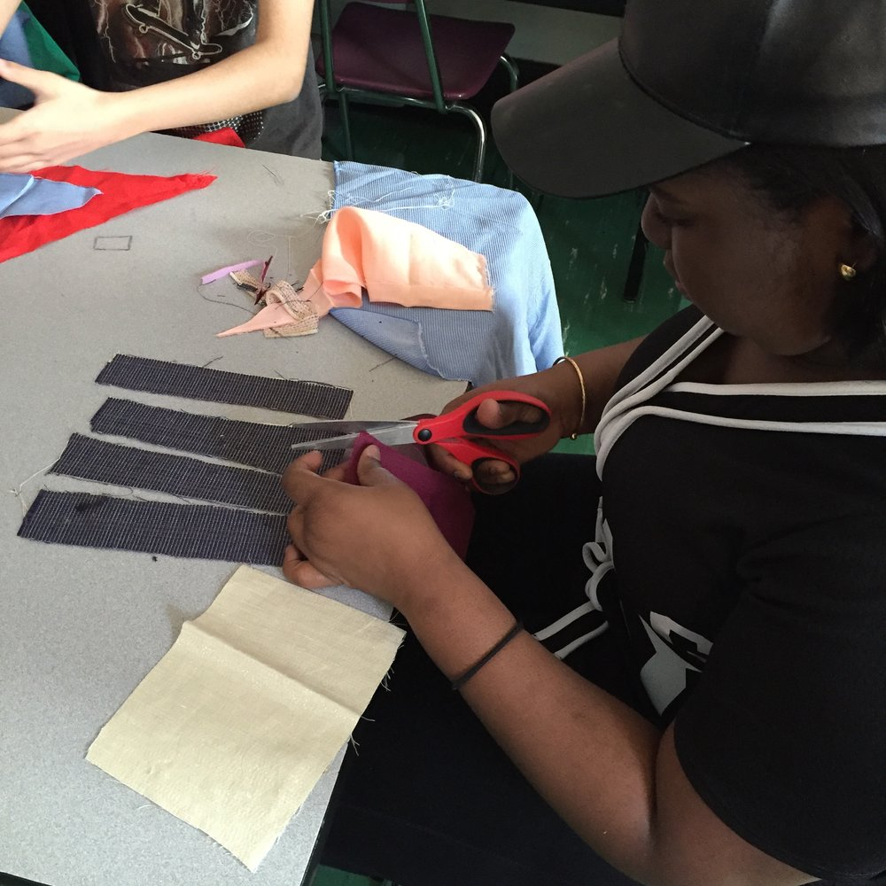 A student cutting her fabric into four long strips.