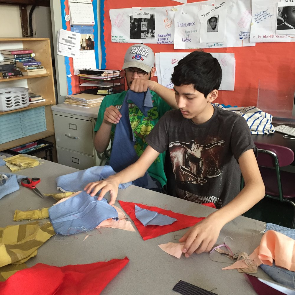 Two students cutting and laying out the composition of their quilt pieces.