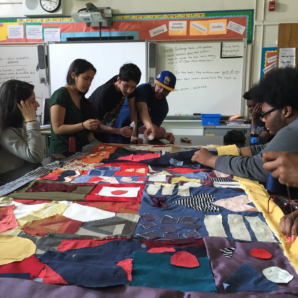 Students around the table hemming the edges of the quilt and planning next steps.
