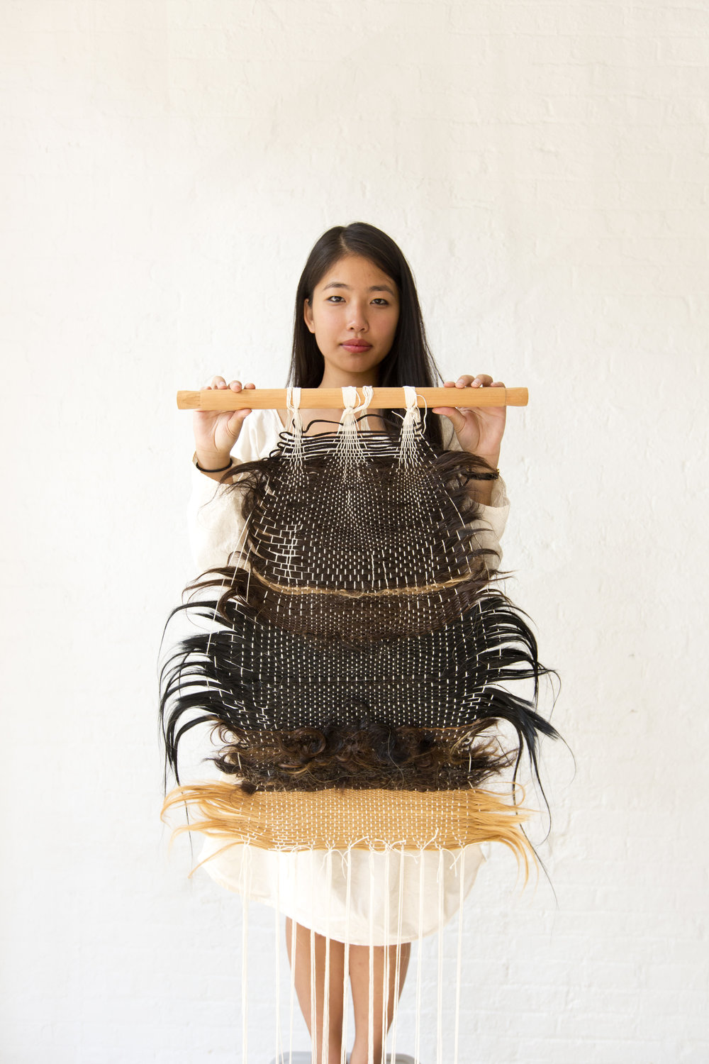 Caption:  Artist holding of a weaving made out of hair donated by 37 people from around the world. The weaving was part of a durational performance called   I hope to Find You at the End of This II   and was woven on a backstrap loom.