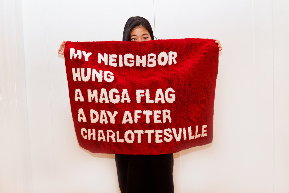 "Artist holding up the rug to cover most of her face, with her eyes and hair exposed. The rug creases at the top to emphasize the words ""My neighbor."""