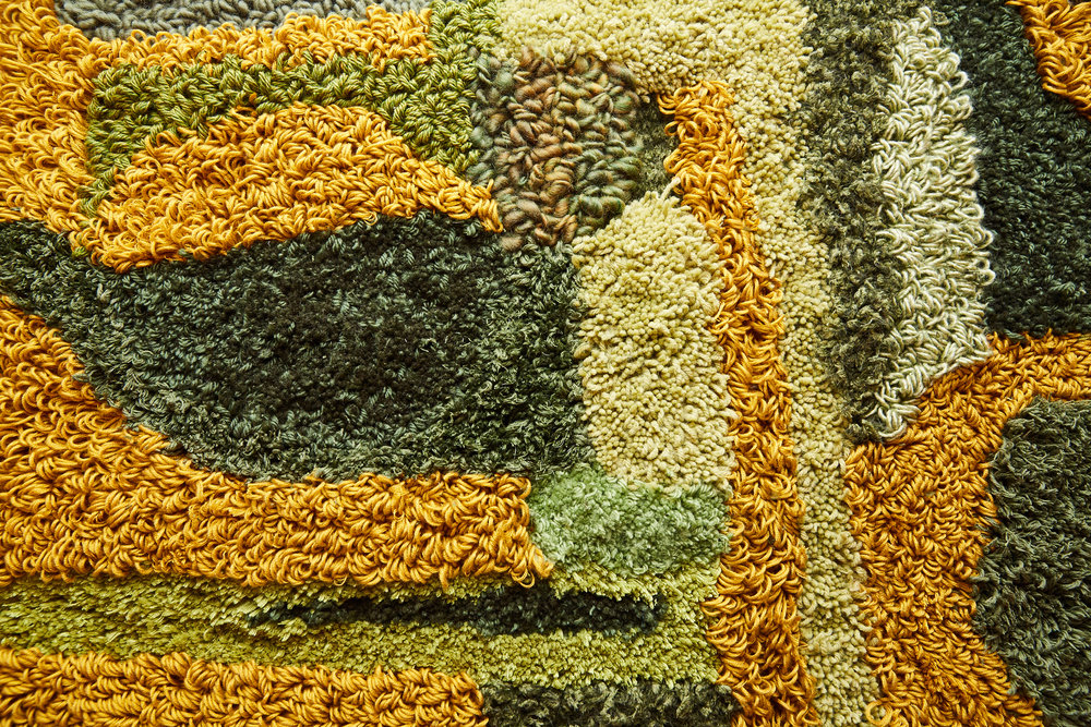 A zoomed-in image of the rug to showcase the different textures and areas of colors. The greens and yellows move organically into one another in different hues.