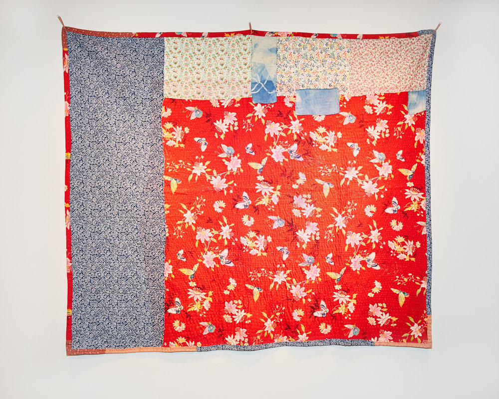 The back of the quilt that's made out of pieces of fabric collected from Vietnam. The largest piece that covers three-fourths of the quilt is in red with repeat prints of flowers and butterflies. The second largest piece moves from the top to bottom left of the quilt is blue with repeat prints of small white flowers. The third piece covers the rest of the quilt is white with repeat prints of small pink and green flowers with leaves. There are three much smaller pieces of natural dyed indigo are used to connect the white fabric with the red one.