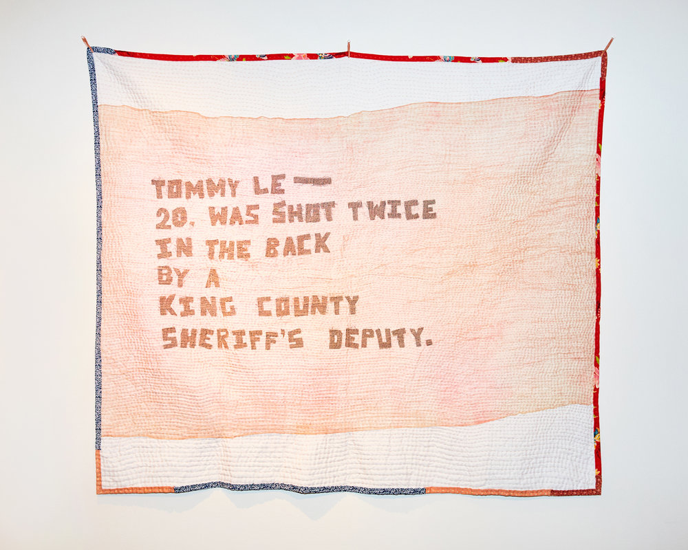 "The front of the quilt consists of hand-cut letters in black on top a white background to read ""Tommy Le—20, was shot twice in the back by a King County Sheriff's Deputy."" An earth tone (pinkish) gauzy fabric is draped on top of the letters. The entire quilt is hand-stitched with horizontal lines. The lines are spaced out at .25 inch."
