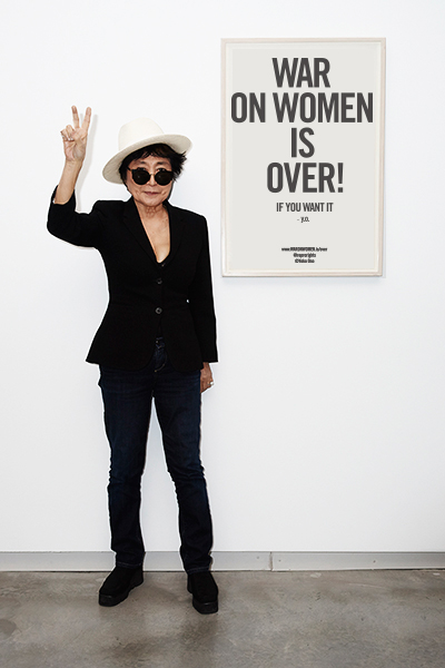 "Yoko Ono holding up a peace sign in front of the ""War on Women is Over! If You Want It"" poster"
