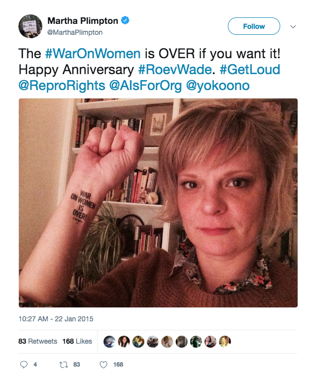 "Actress and activist Martha Plimpton holding up her fist with the ""War on Women is Over! If You Want It"" tattoo on her wrist"