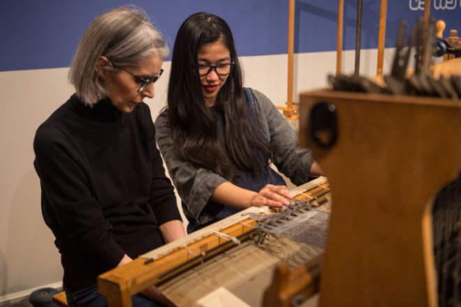 Chi Nguyen teaching a gallery visitor how to weave on a floor loom