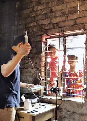 Watchful eyes.  Students in Dhaka, Bangladesh, look on as Stanford researcher Yunjae Hwang sets up air quality measuring equipment inside their home.
