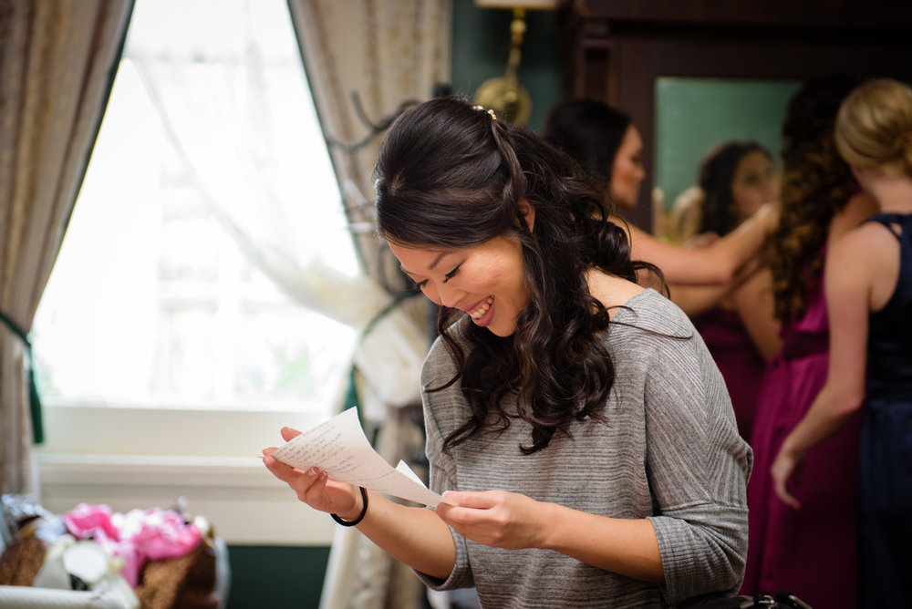 A bride reads a note from her fiancé before their wedding