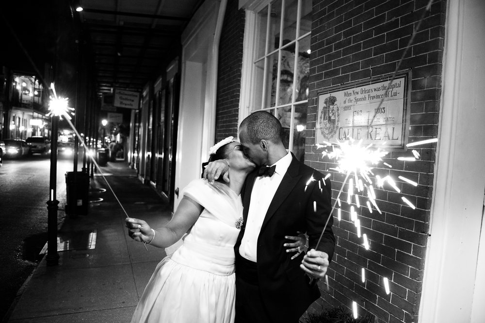 A couple kiss after their wedding reception at Cafe Amelie in the French Quarter, New Orleans