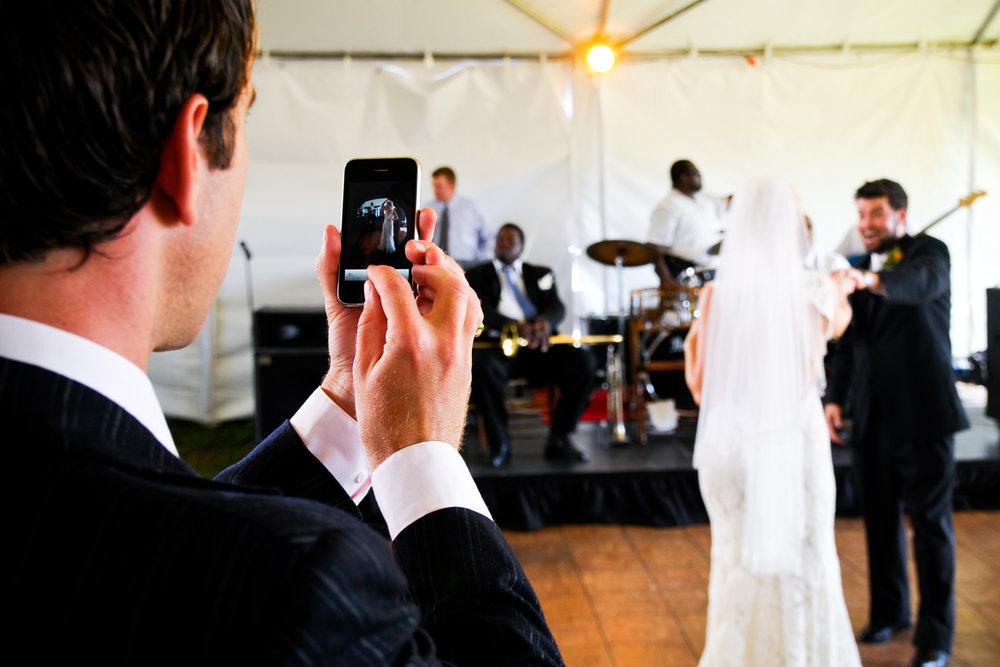 A guest photographs the bride and groom on his iphone in New Orleans
