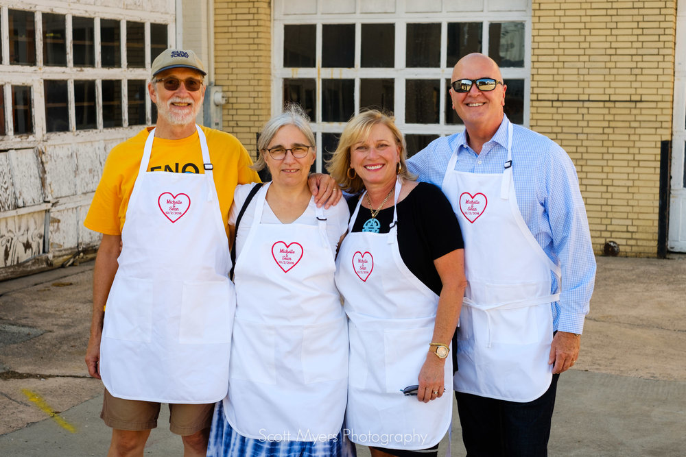 Parents, in their serving aprons for the rehearsal dinner