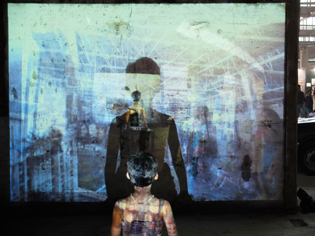 A young girl from Mumbai sits inside the installation, watching the city and her shadow.