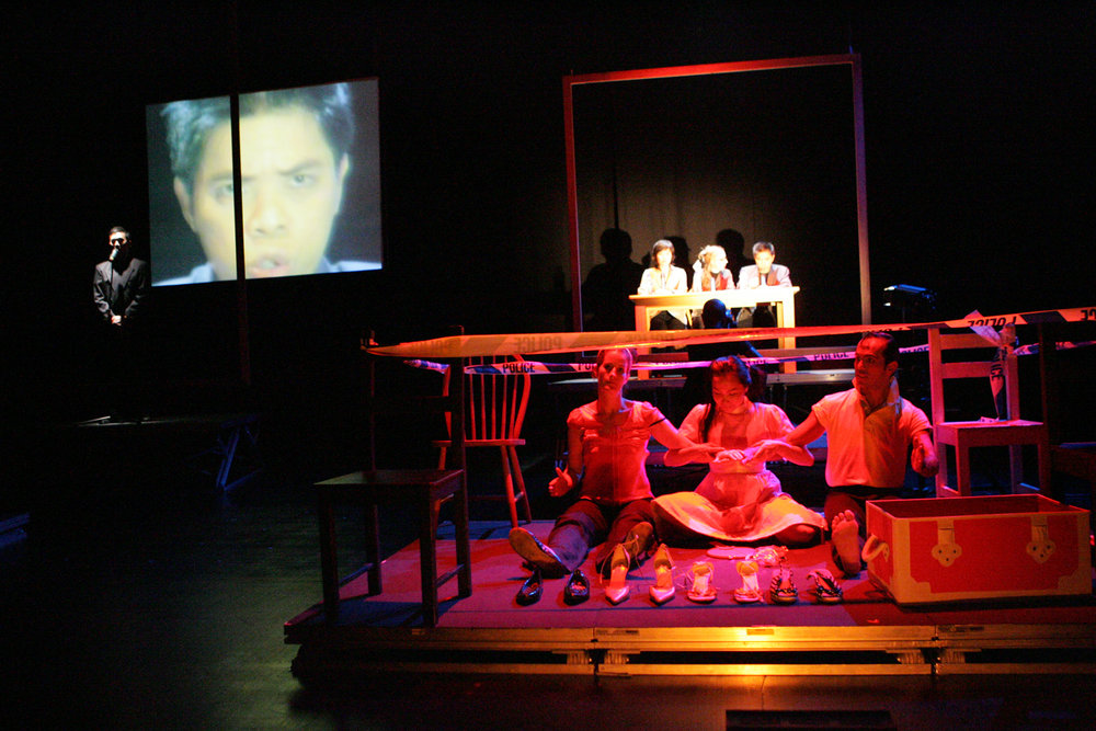 In the foreground during Scenario 11, Amy Ka Man Tam 'plays' Barbie/Ken dolls with Claire Lindsay and Beto Ruiz while the 'panel' in the background (photo above) make pronouncements. Singapore, 2004. Live camera projected each speaker's face onto the large screen as they spoke in turn.