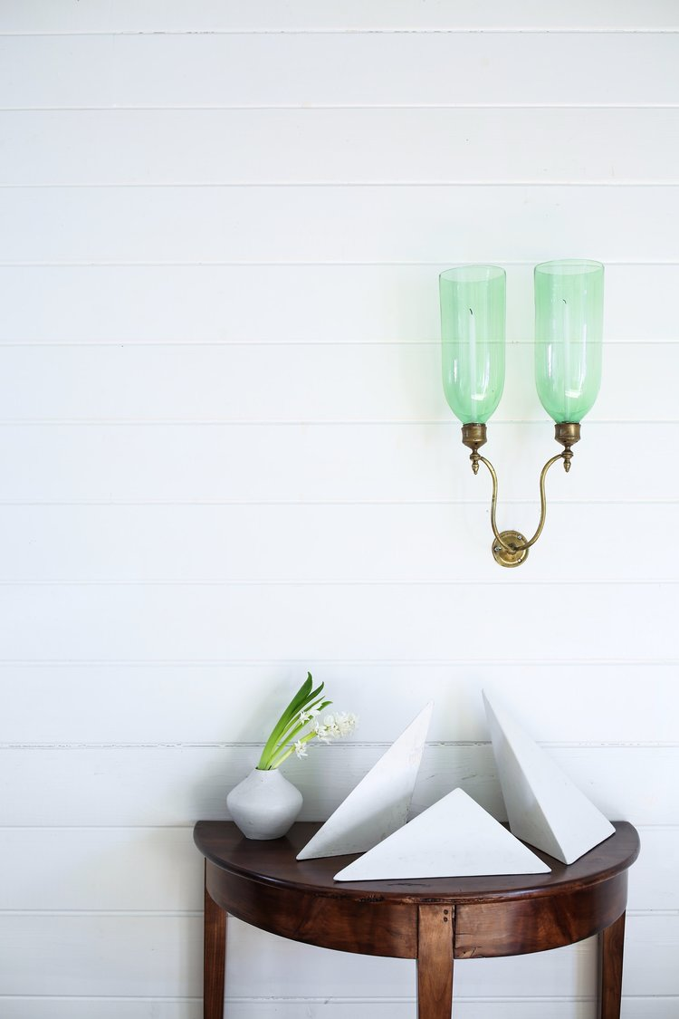 Green glass hurricane sconce contrasts beautifully on a white wall. Geometric forms rest on a demilune table. Classical Interior Designer Amy Meier