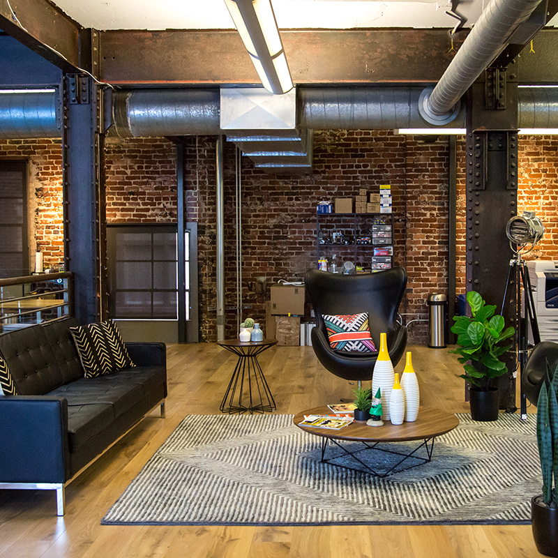 """Beautifully decorated office with brick walls, wood floors, and lots of natural sunlight."""