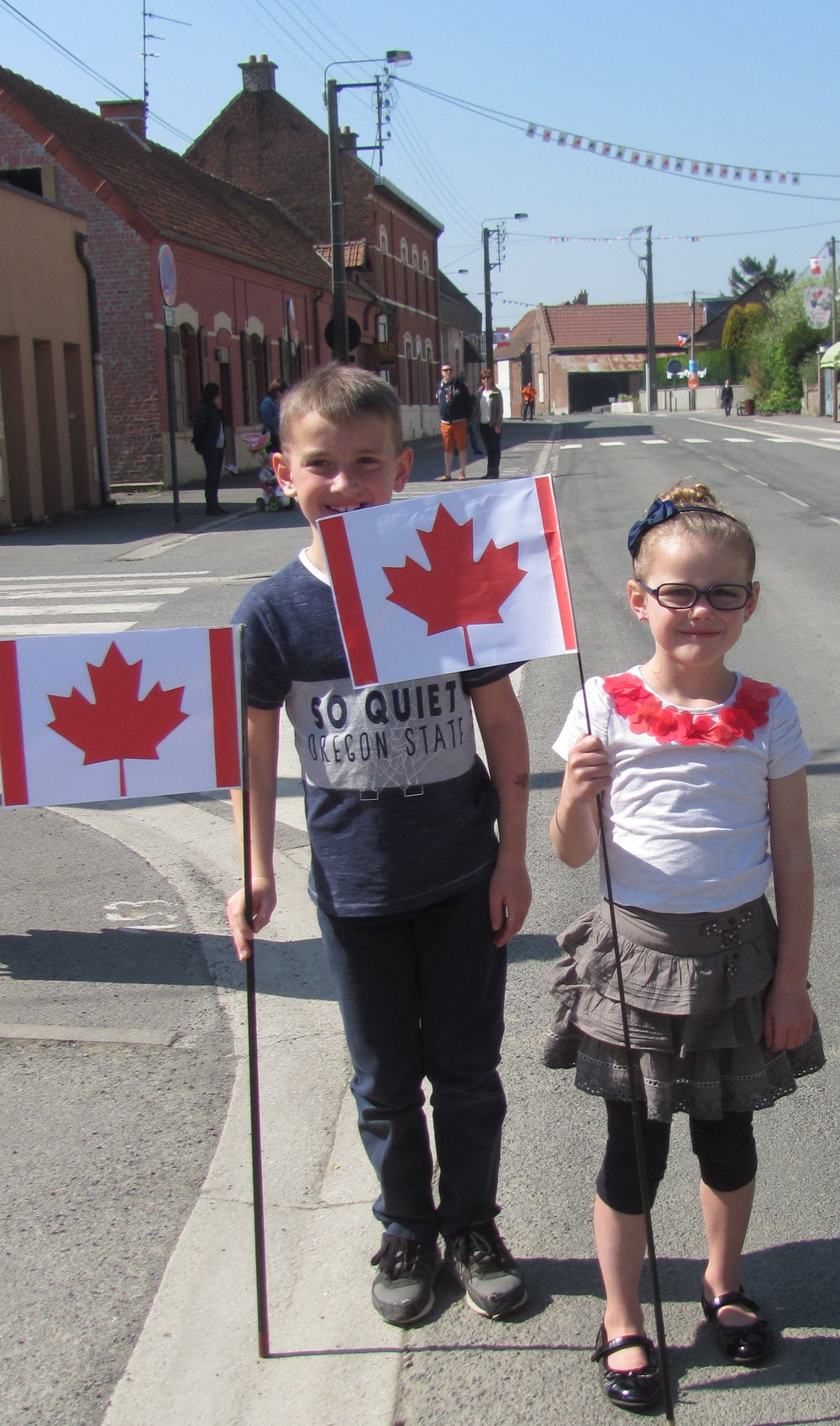 Home made Canadian flags are waved and poppies adorn parade wear.