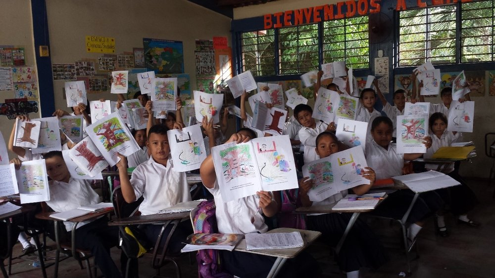 Grade school children hold up the book, Principles that Make you Strong