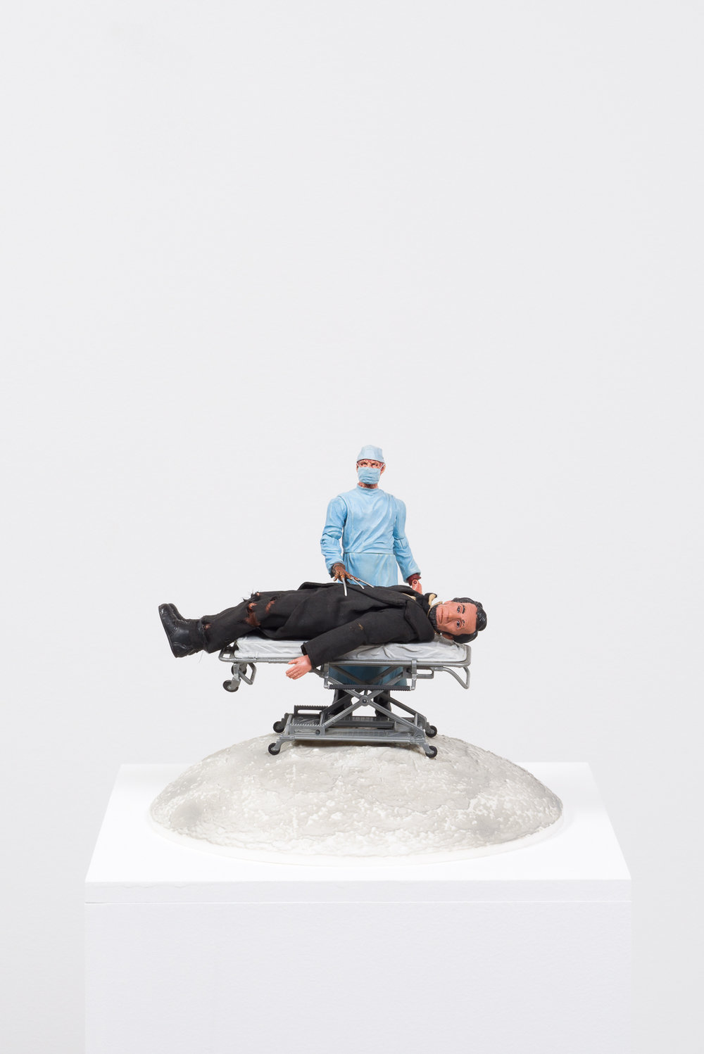 Healthcare Cuts,  2017  Plastic moon model, plastic hospital gurney, plastic and vinyl action figures, pedestal
