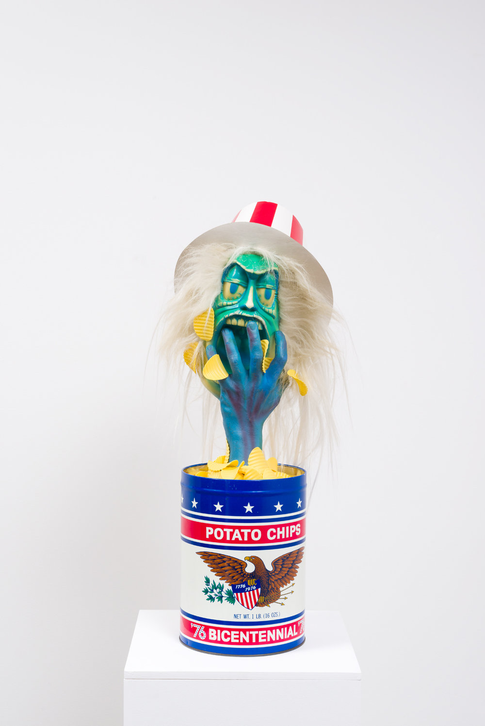 Political Junk Food,  2017  Potato chip tin, plastic potato chips, painted plastic hand and head, wig hair, printed cardboard hat, pedestal