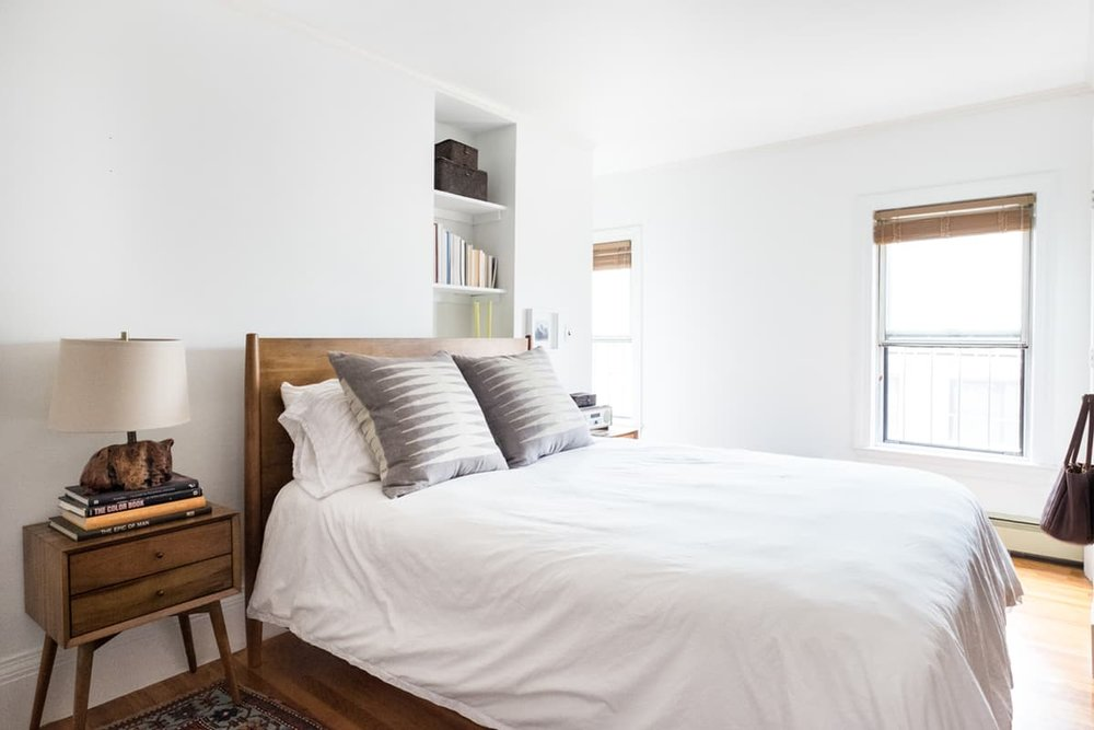 A calm, white bedroom -- with huge windows that let in gorgeous light.