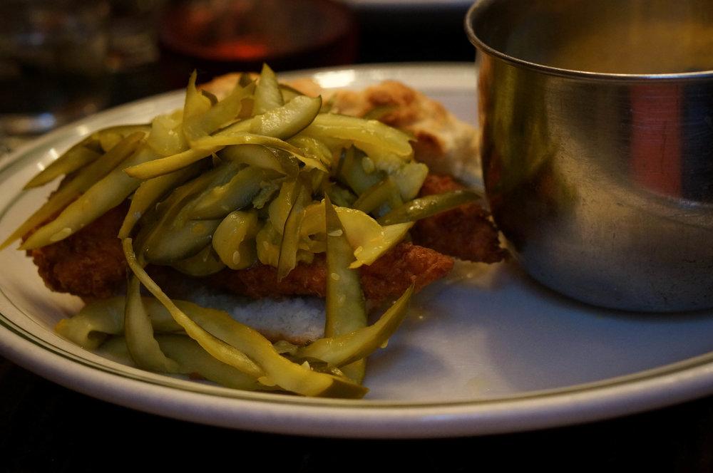 Honey chicken biscuit sandwich with pickles.