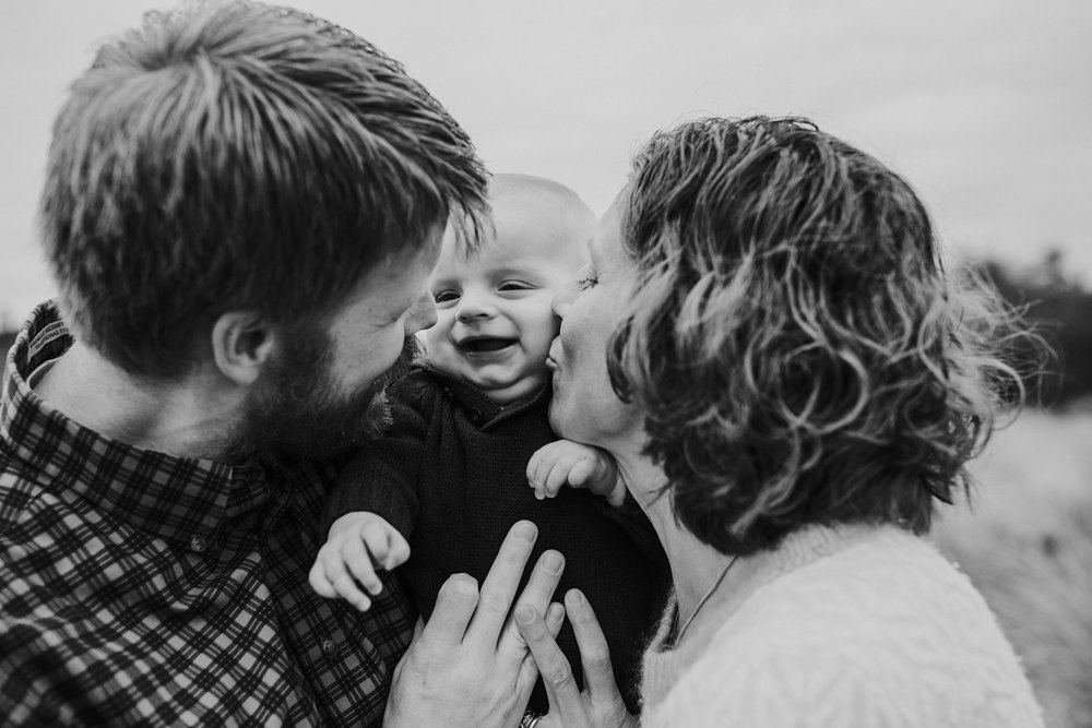 kara chappell whidbey island family photography parents hug and kiss baby boy at deception pass state park