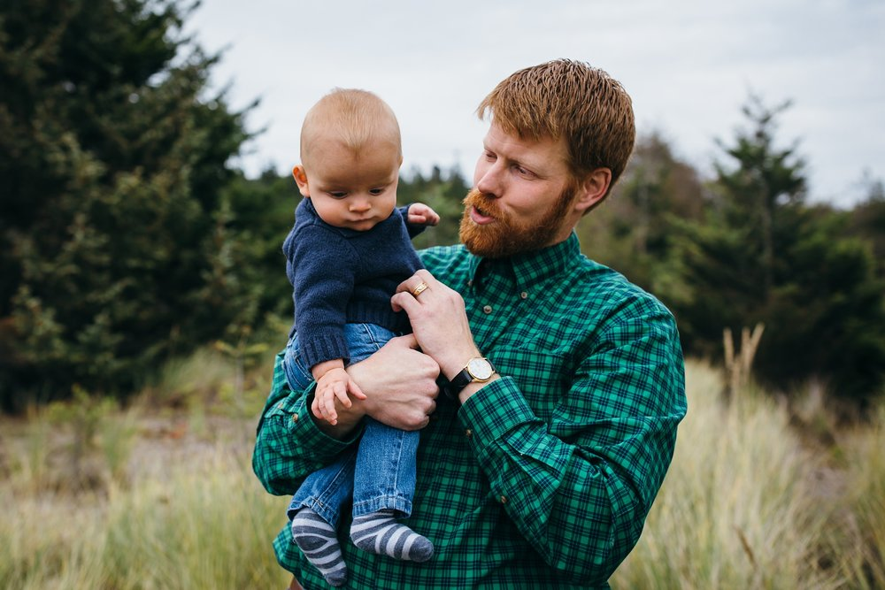 kara chappell whidbey island family photography dad holds baby boy in field at deception pass state park