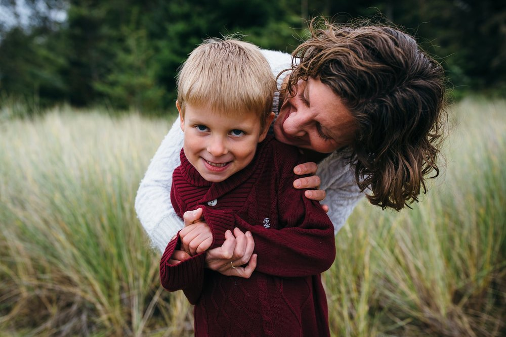 kara chappell whidbey island family photography mom hugs son and whispers in his ear