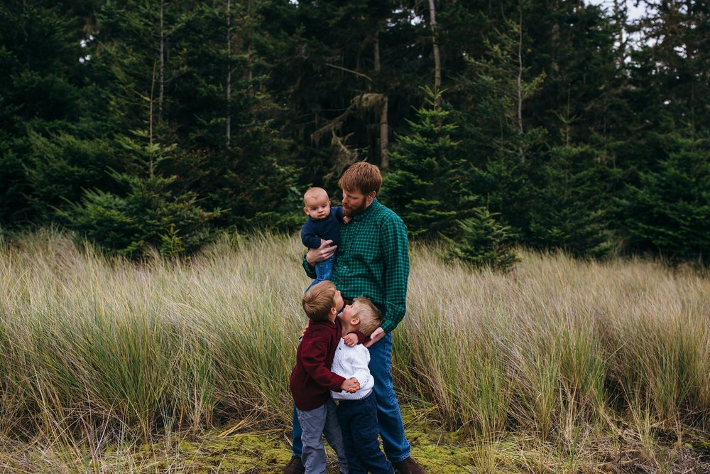 kara chappell whidbey island family photography dad hugs three sons in field at washington beach