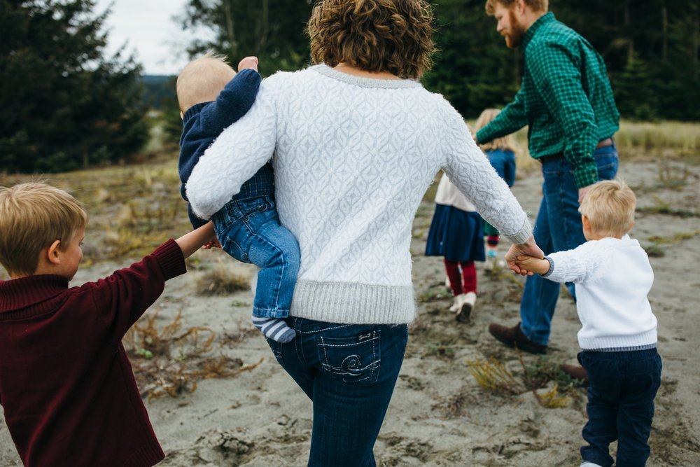 kara chappell whidbey island family photography family holds hands and walks through field