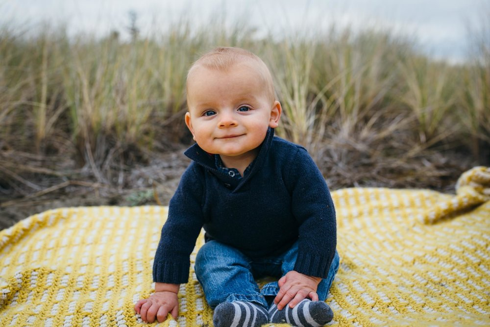 kara chappell whidbey island family photography baby boy sits on yellow blanket at beach