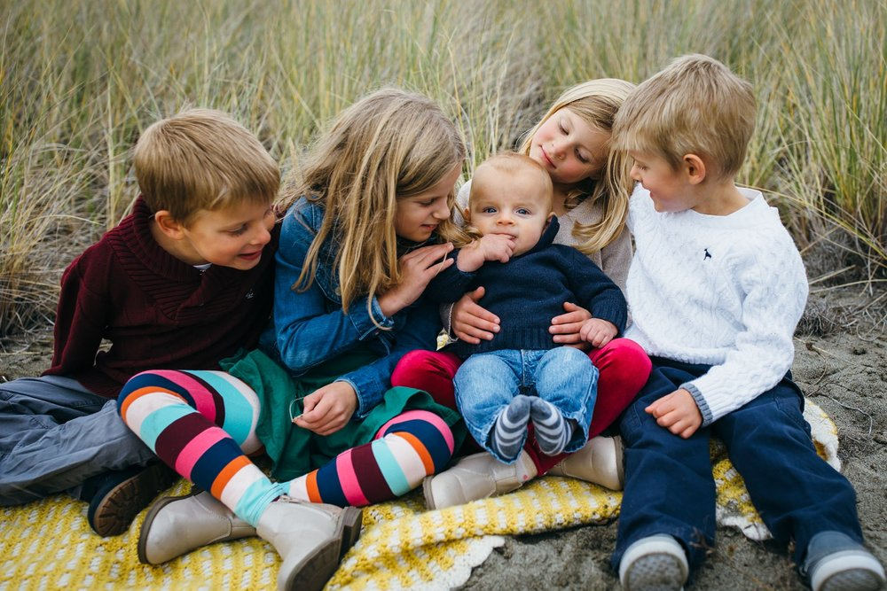 kara chappell whidbey island family photography siblings sit on blanket and look at baby brother