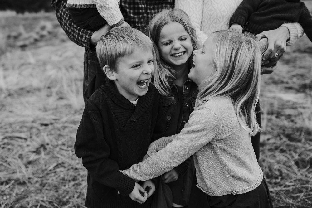 kara chappell whidbey island family photography siblings laugh at jokes during family pictures at deception pass