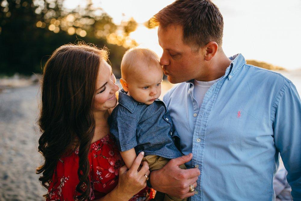 Parents kiss baby on cheek at Deception Pass