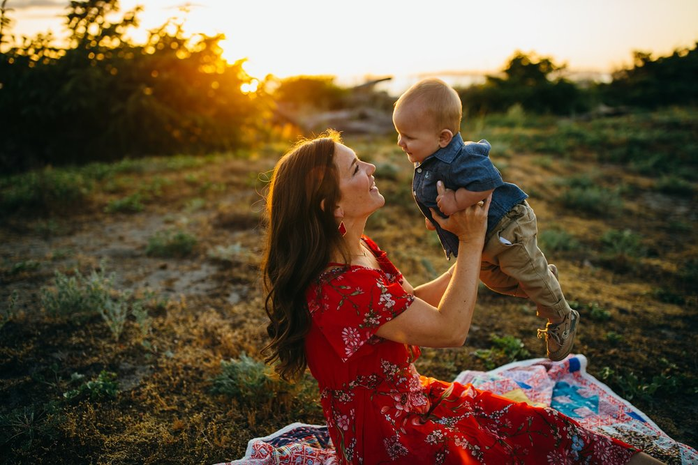 Mother holds baby in air at park | Whidbey Island Family Photographer