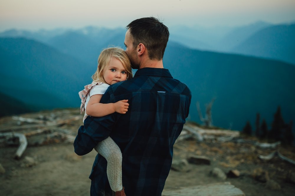 father holds daughter on top of mountain at olympic national forest