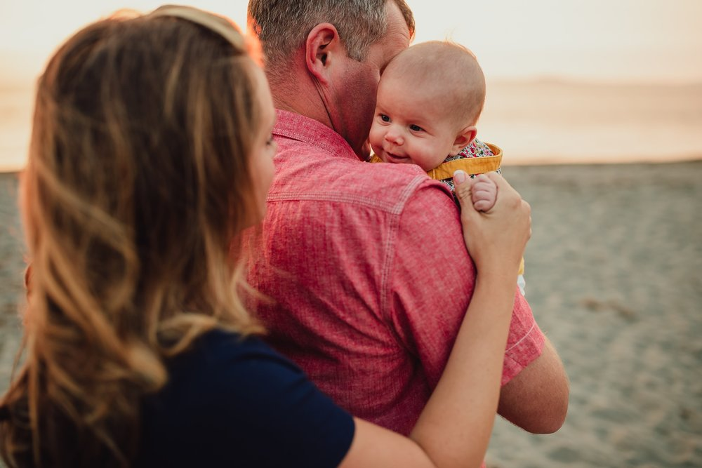 mom holds baby's hand on beach | Whidbey Island family photographer