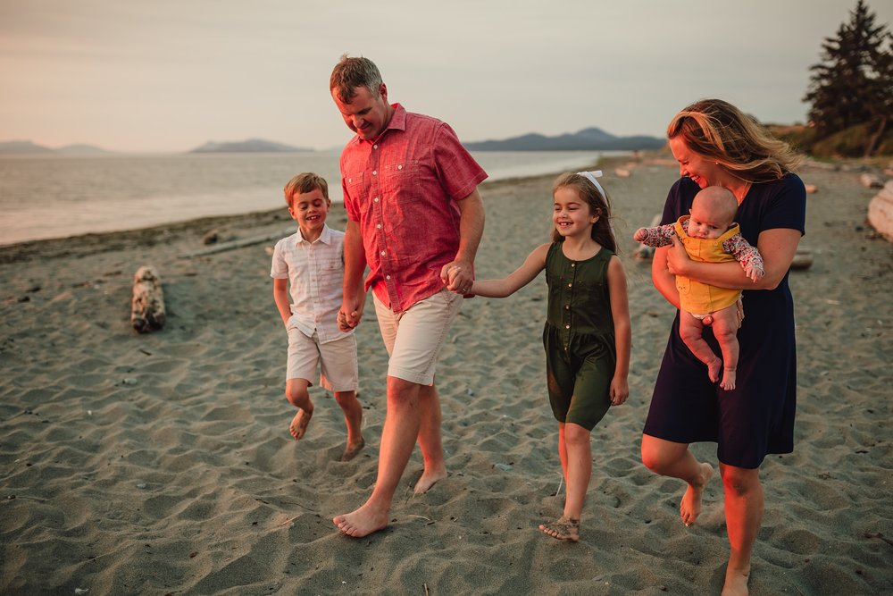 family walks down Whidbey Island beach during portrait session