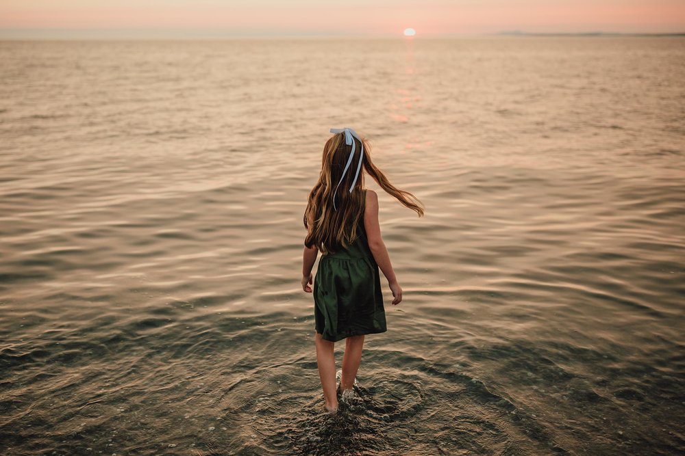 Girl wades into ocean during family pictures at sunset on Washington beach