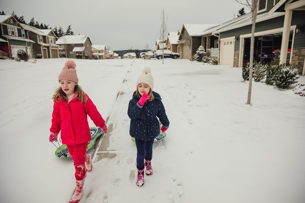 girls walk through snow with sleds | Whidbey Island family photographer