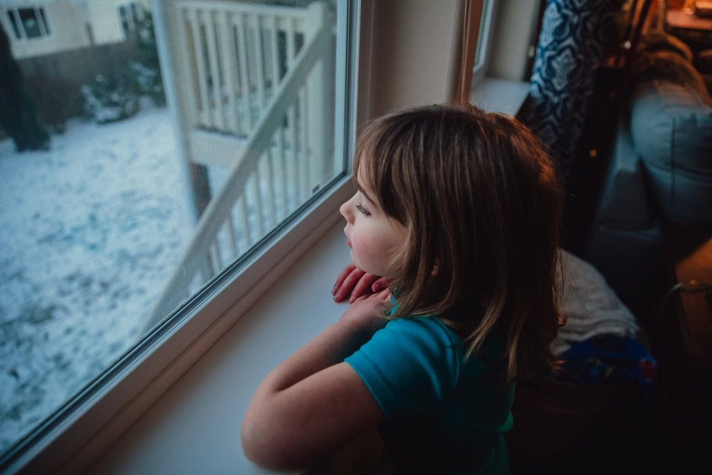 young girl looks out window at snow in Washington | Whidbey Island family photographer